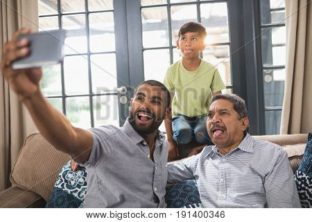 Happy multi-generation family making face while taking selfie together at home