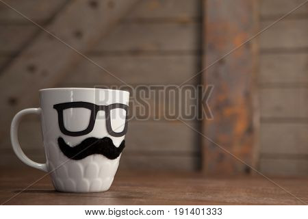 Close-up of fake moustache and spectacles on mug