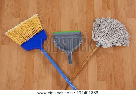 Dustpan, sweeping broom and mop on wooden floor