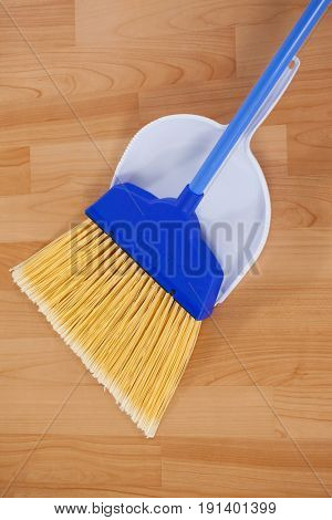Close-up of sweeping broom with dustpan on wooden floor