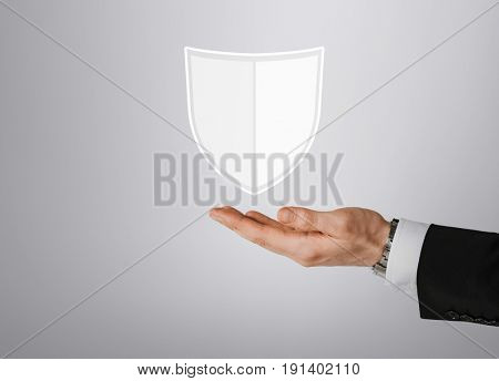 business, people and cyber protection concept - close up of male hand with virtual antivirus program shield icon over gray background