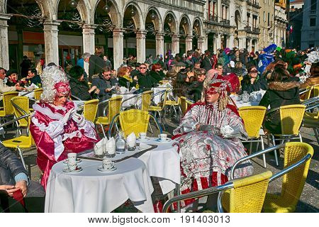 VENICE, ITALY - FEBRUARY 8, 2015: Tourists and masked persons in colorful costume sitting in cafe on San Marco Square during the Carnival in Venice, Italy.