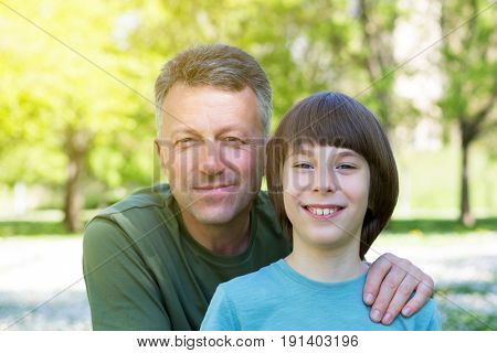 Father and son posing together over sunny spring park outdoor. Family look. Dad hugs his teen son outdoor.