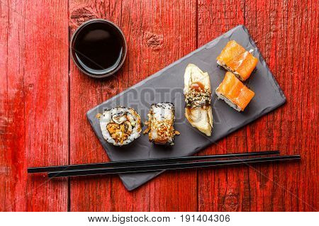 Photo of rolls with chopsticks, soy sauce on red wooden table