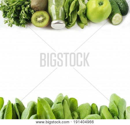 Spinach smoothie and vegetables at border of image with copy space for text. Green smoothie with apples parsley spinach cucumber and kiwi on a white background. Top view. Fruit on white background.