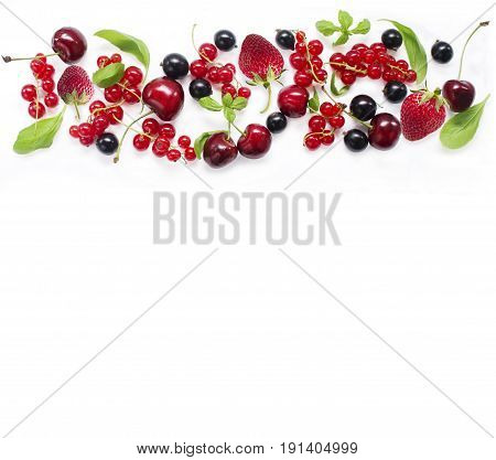 Top view. Various fresh summer berries on white background. Ripe cherries currants strawberries mint and basil leaves. Berries at border of image with copy space for text. Background berries.