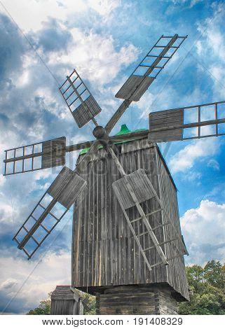 Old wooden windmill on blue sky background, Ukraine