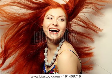 Beautiful young happy woman with long flowing red hair