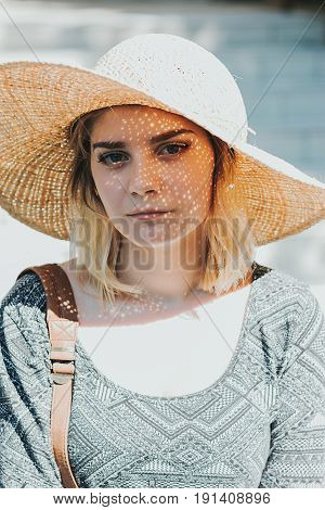 Cute girl wearing big summer hat pretending to be woman lady. Sunny
