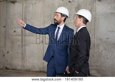 Two professional architects in hard hats discussing project and looking away