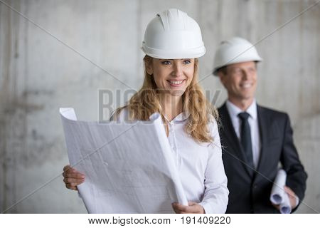 Smiling middle aged businesswoman holding blueprint while smiling colleague standing behind