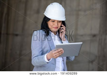Professional Middle Aged Businesswoman In Hard Hat Talking On Smartphone And Using Digital Tablet