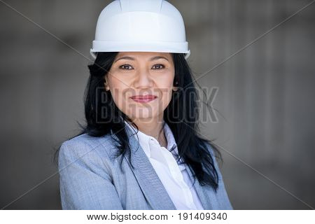 Beautiful Mature Asian Businesswoman In Hard Hat Smiling At Camera