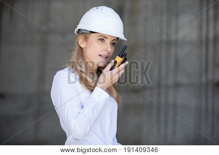 Professional Middle Aged Engineer In Hard Hat Using Walkie-talkie While Working