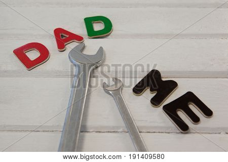 Wrench, screwdriver with text dad and me on wooden plank