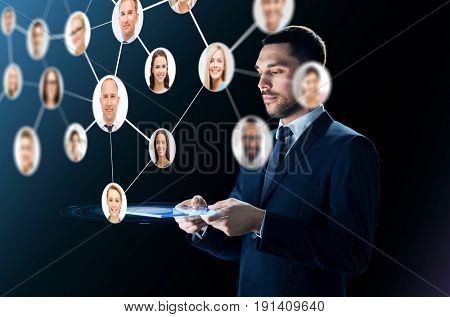 business, people, headhunting, communication and modern technology concept - businessman in suit working with transparent tablet pc computer and contacts network over black background