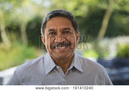 Portrait of smiling senior man at porch