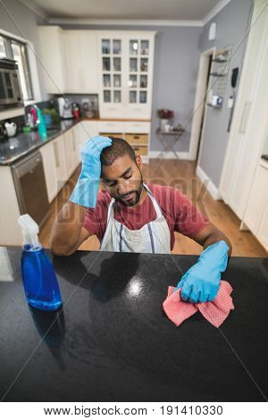 High angle view of tensed young man by marble counter in kitchen at home