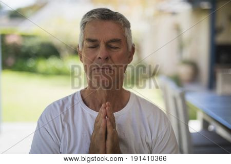 Senior man with eyes closed meditating at porch