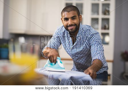 Portrait of smiling young man ironing cloth in domestic kitchen at home