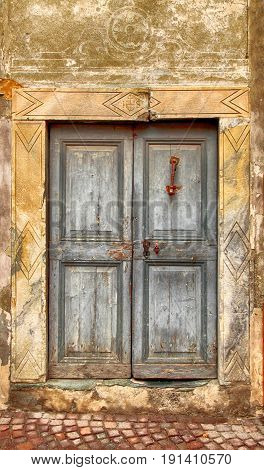 Vintage grey damaged wood medieval door in rural stone wall house, Italy.