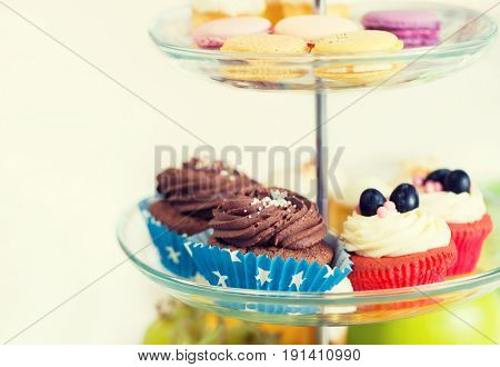 unhealthy eating, sweets, dessert, baking and junk food concept - close up of cake stand with cupcakes and cookies