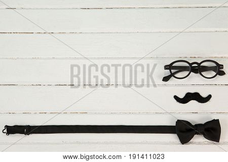 Close-up of bow tie, spectacles and fake moustache arranged on wooden plank