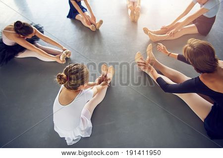 Girls With Teacher Sitting And Stretching In Ballet Class
