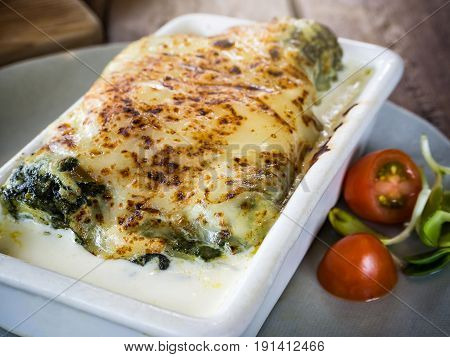 Lasagna In Ceramic Casserole Dish Served With Tomato And Herb, Italian Food