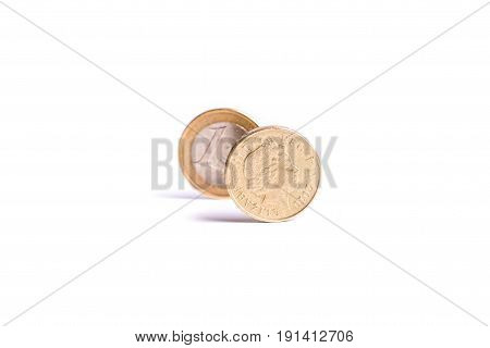 One Pound Coin Stand In Front Of The One Euro Coin On White Background