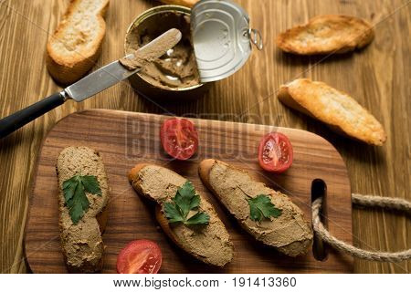 Liver pate on the bread on wooden board.