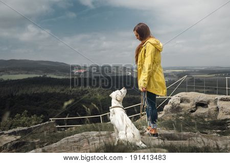 young woman and cute labrador retriever dog puppy during a hike on a mountain in front of blue sky