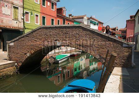 BURANO, ITALY - MAY 23, 2017: Bridge in the canal of Burano island, Italy