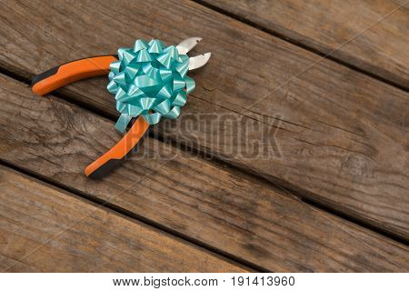 Close-up of decorated pliers on wooden plank