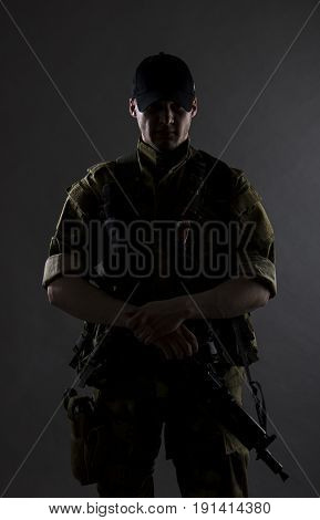 A military mistical portrait. The military man is standing with gun.