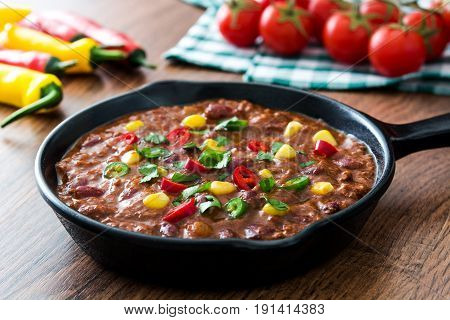 Traditional mexican tex mex chili con carne in a frying pan on wooden table