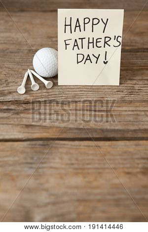 Happy fathers day message with sports equipments on wooden plank