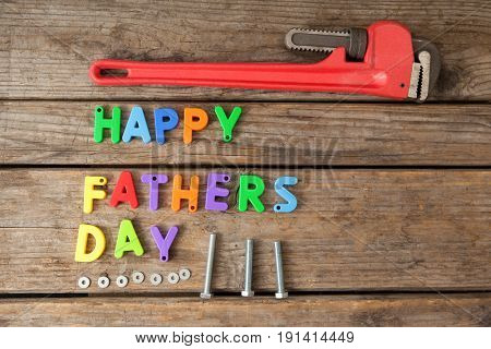 Close-up of happy fathers day blocks and handtools on wooden plank