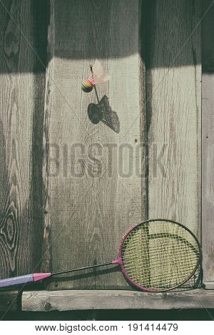 Old ball and racket of badminton hanging on a wooden wall with a shadow on a summer day
