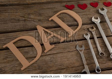 Close-up of various wrenches and text dad on wooden plank