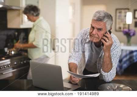 Portrait of senior man talking on phone while wife cooking in kitchen at home