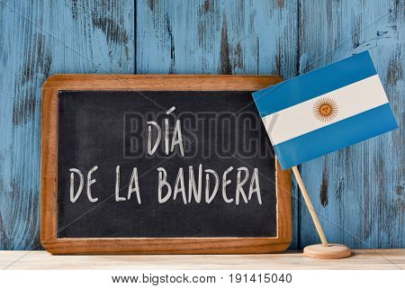 the text Dia de la Bandera, Flag Day written in Spanish in a chalkboard, and a flag of Argentina, on a rustic wooden surface, against a blue wooden background