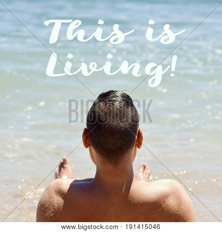closeup of a young caucasian man seen from behind lying down face up on the sand in the seashore and the text this is living