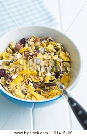Tasty homemade muesli with nuts in bowl on white table.