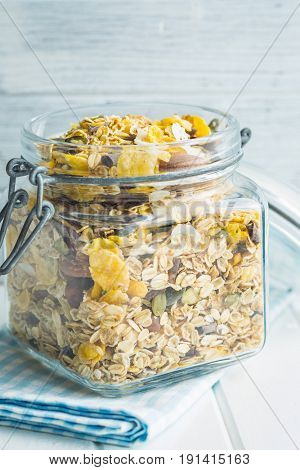 Tasty homemade muesli with nuts in jar on white table.