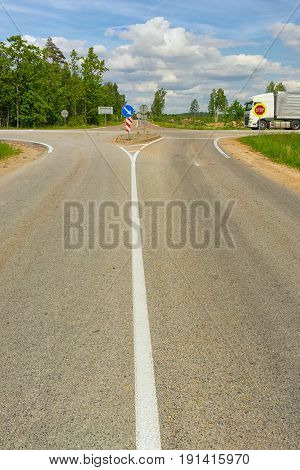 Crossroads of asphalt roads with road signs and a truck in years