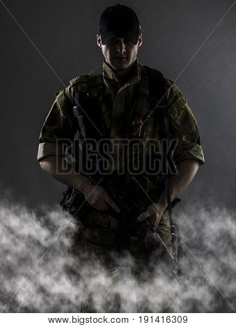A military mistical portrait. The military man is standing with gun in fog.