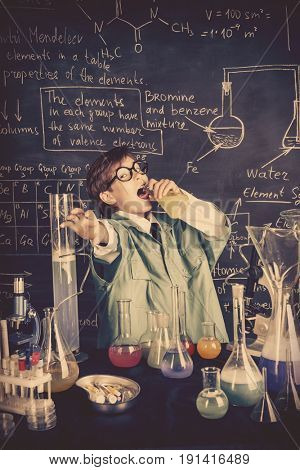 The boy scientist is going to drink the chemical solution he invented. Educational concept. Discovery.