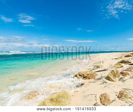White sandy beach with waves breaking on the shoreline