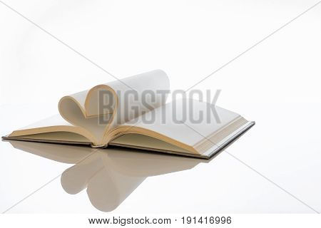 Open book blank pages folded into heart shape with reflection and white space.